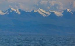 De bergen in de nevel van het meer met een boot Royalty-vrije Stock Foto