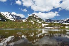 De bergen, het meer en de wolken van Kamchatka in blauwe hemel op zonnige dag Royalty-vrije Stock Foto