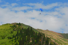 De bergen van Alma Ata met paraplane die in de hemel vliegen Stock Afbeelding