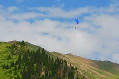 De bergen van Alma Ata met paraplane die in de hemel vliegen Royalty-vrije Stock Foto