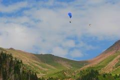 De bergen van Alma Ata met paraplane die in de hemel vliegen Stock Afbeeldingen