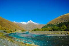 De bergen van de Kaukasus in de zomer, groene heuvels, blauwe hemel en sneeuw piekmkinvari weg van Gudauri aan Stepantsminda stock foto's