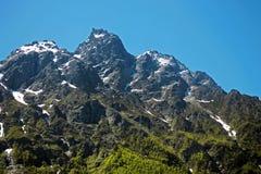 De bergen van de Kaukasus onder sneeuw en duidelijke blauwe hemel Stock Afbeeldingen