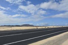 De bergen van de woestijnweg en bewolkte hemel Royalty-vrije Stock Foto's
