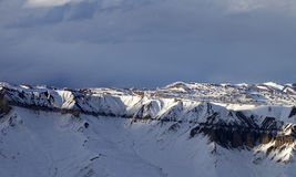 De bergen van de zonlichtwinter en donkere wolken bij avond Royalty-vrije Stock Foto