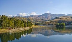 De bergen van Drakensberg die van een meer worden weerspiegeld stock foto's