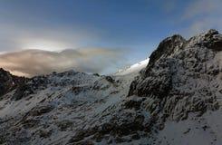 De bergen van de winter Wolken door de Wind over de Top worden geblazen die royalty-vrije stock afbeeldingen