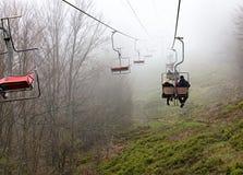 De berglift vervoert toeristen aan de nevelige berg Royalty-vrije Stock Afbeeldingen