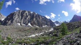 De bergrivier loopt langs de vallei De steile berg Weergeven van de sneeuwpieken stock videobeelden