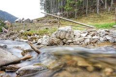De bergstroom in het bos, bij de bodem is stenen Dichtbij weilandomheining voor vee stock foto