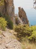 De bergweg daalt naar de free-standing smalle rotsen die van het water uitpuilen Stock Foto's