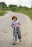 De berijdende autoped van het meisjeskind op de weg in het platteland, kind Stock Afbeelding