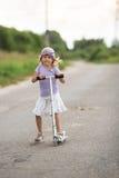 De berijdende autoped van het meisjeskind op de weg in het platteland, kind Stock Foto's
