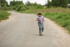 De berijdende autoped van het meisjeskind op de weg in het platteland, kind Stock Foto