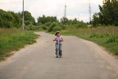 De berijdende autoped van het meisjeskind op de weg in het platteland, kind Royalty-vrije Stock Foto's