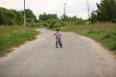 De berijdende autoped van het meisjeskind op weg op plattelandsgebieden, concept c Stock Fotografie