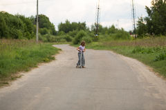 De berijdende autoped van het meisjeskind op weg op plattelandsgebieden, concept c Royalty-vrije Stock Afbeelding