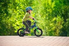 De berijdende fiets van de jongen in een helm Stock Fotografie