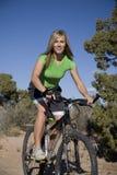 De berijdende fiets van de vrouw op sleep. Stock Foto