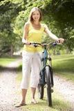 De berijdende fiets van de vrouw in platteland Stock Foto's