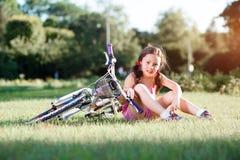 De berijdende fiets van het kindmeisje op de zomerzonsondergang in het park Stock Afbeelding