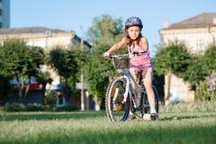 De berijdende fiets van het kindmeisje op de zomerzonsondergang in het park Royalty-vrije Stock Foto