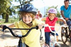 De berijdende fietsen die van de familie pret hebben Stock Foto's