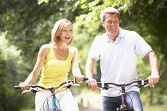 De berijdende fietsen van het paar in platteland Royalty-vrije Stock Fotografie
