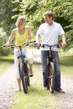 De berijdende fietsen van het paar in platteland Stock Foto