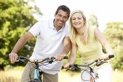 De berijdende fietsen van het paar in platteland Royalty-vrije Stock Afbeeldingen