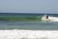 De berijdende golf van Surfer Stock Afbeeldingen