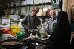 De beroemde Iraanse marktbazaar en een vrouw in een zwarte chodor kopen producten stock afbeelding