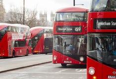 De beroemde rode bussen van Londen op de straten van de stad van Londen Huizen van het Parlement op achtergrond Stock Fotografie