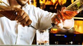 De beroeps bij de bar bereidt gemengde dranken voor zijn gasten voor Royalty-vrije Stock Foto