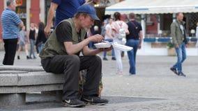 De berooide dakloze mens eet van plastic plaatzitting op de straat stock videobeelden