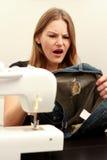 De beschadigde jeans van de vrouw holding en het kijken geschokt Royalty-vrije Stock Fotografie