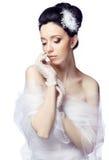 De bescheiden jonge vrouw die op witte studioachtergrond wordt geïsoleerd kleedde zich in de kaap van organza en kanthandschoenen Royalty-vrije Stock Afbeelding