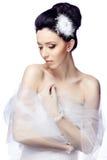 De bescheiden jonge vrouw die op witte studioachtergrond wordt geïsoleerd kleedde zich in de kaap van organza en kanthandschoenen Royalty-vrije Stock Afbeeldingen