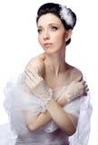 De bescheiden jonge vrouw die op witte studioachtergrond wordt geïsoleerd kleedde zich in de kaap van organza en kanthandschoenen Stock Foto's