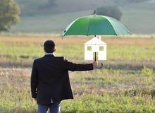 De beschermingsconcept van de huisverzekering, zakenman met paraplu Stock Foto's