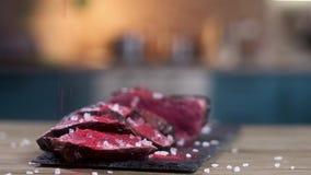 De besnoeiing in plakken gebraden vleeschef-kok bestrooit Spaanse peper en paprikahanden close-up, Langzame motie stock video