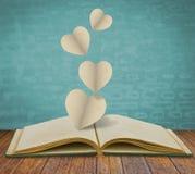 De besnoeiing van het document van hart op boek Royalty-vrije Stock Foto