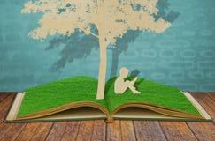 De besnoeiing van het document van kinderen las een boek onder boom. stock foto's