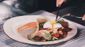De besnoeiing van vrouwen` s handen stroopte ei in salade met mes en vork Clouse omhoog stock video