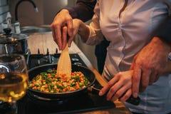 De besnoeiingsmening en sluit omhoog Man die vrouw helpen om diner te koken Hij houdt zijn handson van haar Zij verenigen zich bi stock foto's
