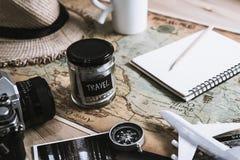 De besparing van het vakantiegeld in een glas met camera op kaart Stock Afbeeldingen