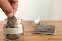 De besparingenconcept van het geld Het verzamelen van geld in de geldkruik voor uw concept het muntstuk van de handholding, Geldk stock foto's
