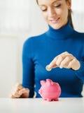 De besparingsgeld van de vrouw in spaarvarken Stock Afbeeldingen