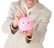De besparingsgeld van de zakenman in een piggy-bank royalty-vrije stock foto