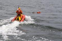 De besparingspersoon van Rescuerunner in water Stock Afbeeldingen